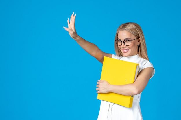 フォルダーを保持し、青い壁に手を振って白いドレスを着た女性労働者の正面図