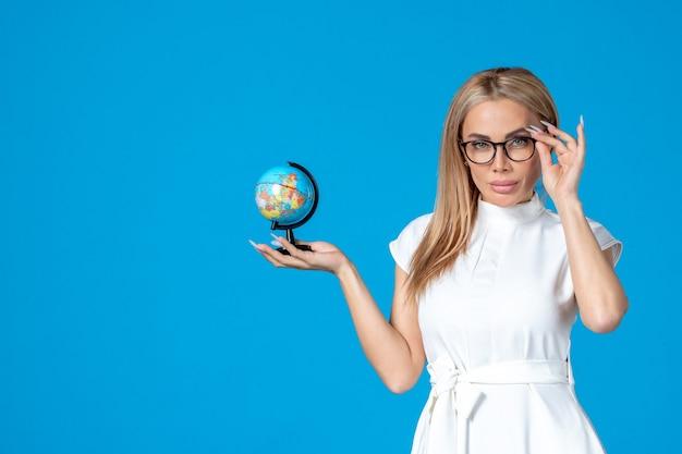 青い壁に小さな地球儀を保持している白いドレスを着た女性労働者の正面図
