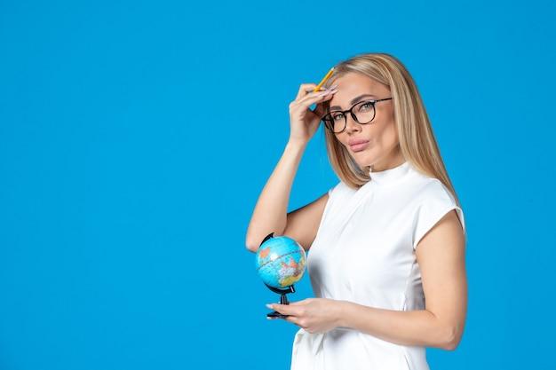 파란 벽에 작은 지구 지구를 들고 흰 드레스를 입은 여성 노동자의 전면 모습