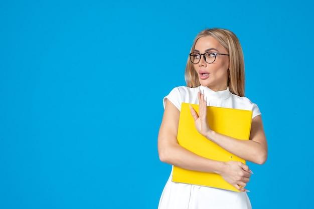 파란 벽에 노란색 폴더를 들고 있는 흰 드레스를 입은 여성 노동자의 전면 모습