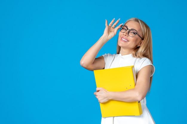 Вид спереди работницы в белом платье, держащей желтую папку на синей стене