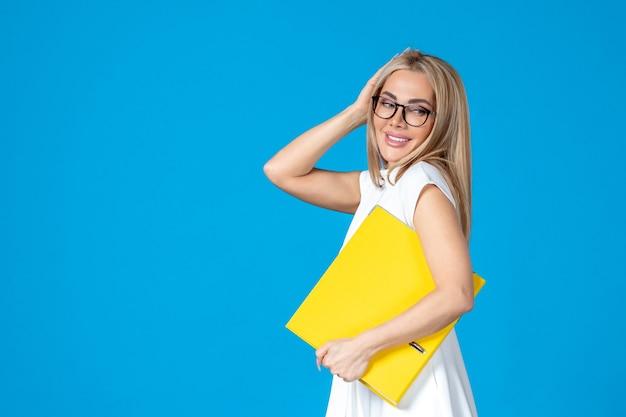 青い壁に黄色のフォルダーを保持している白いドレスの女性労働者の正面図