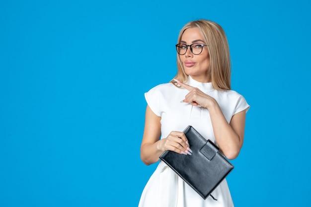 Вид спереди работницы в белом платье, позирующей с блокнотом на синей стене
