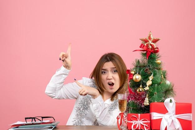 ピンクのプレゼントと彼女のテーブルの後ろに座っている女性労働者の正面図