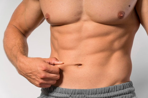 腹筋を示すフィット上半身裸の男の正面図
