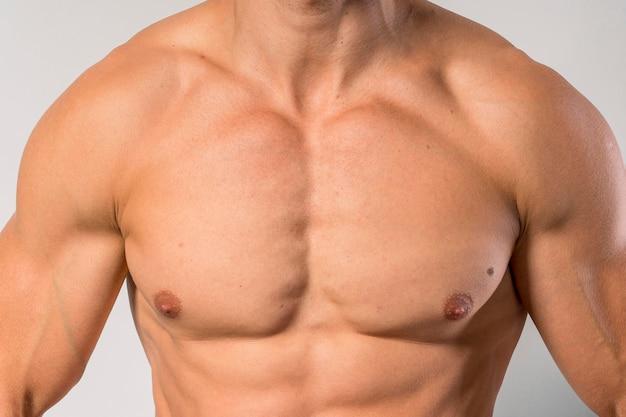 Вид спереди подтянутого человека без рубашки, показывающего грудные мышцы