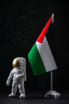 Вид спереди флага палестины с игрушкой космонавта на черном