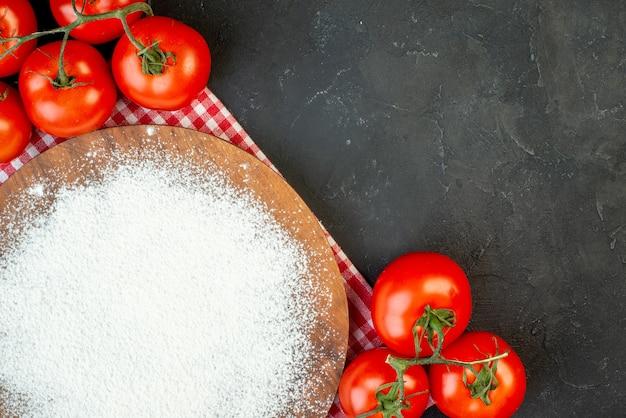빨간색 벗겨진 수건에 있는 커팅 보드에 있는 밀가루와 검은 배경에 줄기가 있는 신선한 토마토의 전면 보기