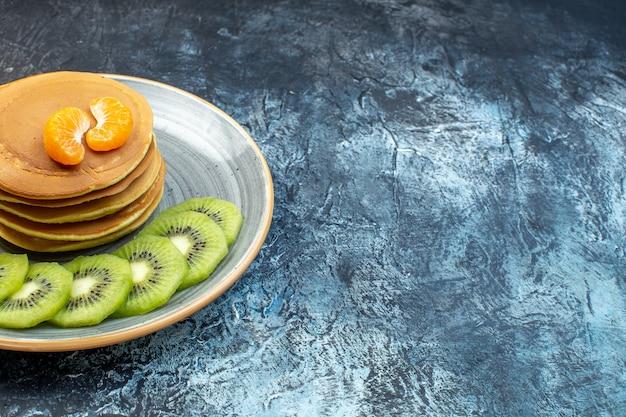 얼음 배경의 오른쪽 접시에 키위 과일과 귤과 함께 제공되는 천연 요구르트로 만든 푹신한 미국식 팬케이크의 전면 전망