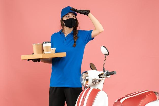 パステル ピーチ色の背景にコーヒーの小さなケーキを保持しているオートバイの隣に立っている医療マスク手袋を着た宅配便の女の子の正面図