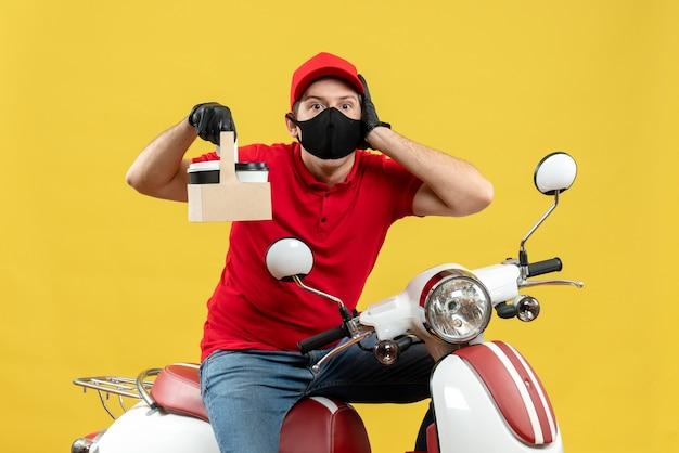 注文を示すスクーターに座っている医療マスクで赤いブラウスと帽子の手袋を着用して焦点を当てた宅配便の男の正面図