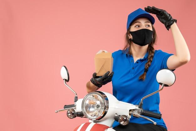 桃の背景に小さな箱を保持している黒い医療用マスクと手袋を着た女性宅配便の正面図