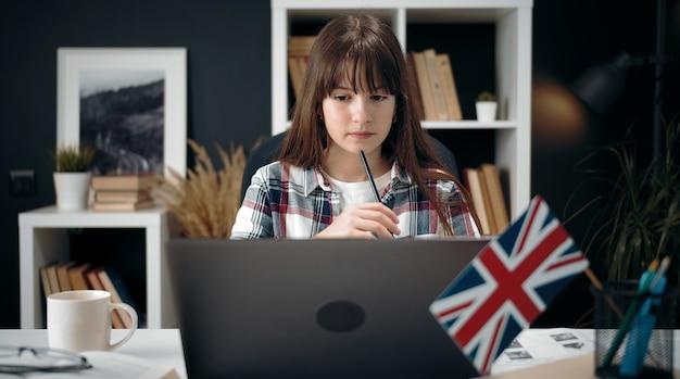 自宅のテーブルに座ってラップトップ、遠隔教育で勉強している焦点を当てた10代の少女の正面図