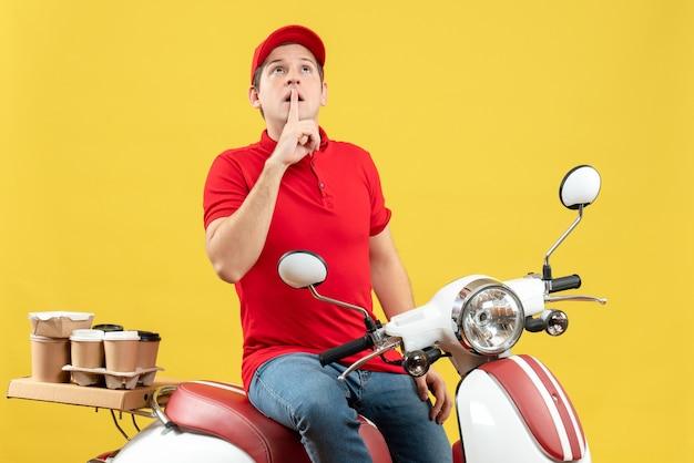 赤いブラウスと帽子をかぶって、黄色の背景に沈黙のジェスチャーをする注文を配信する焦点を当てた若い男の正面図