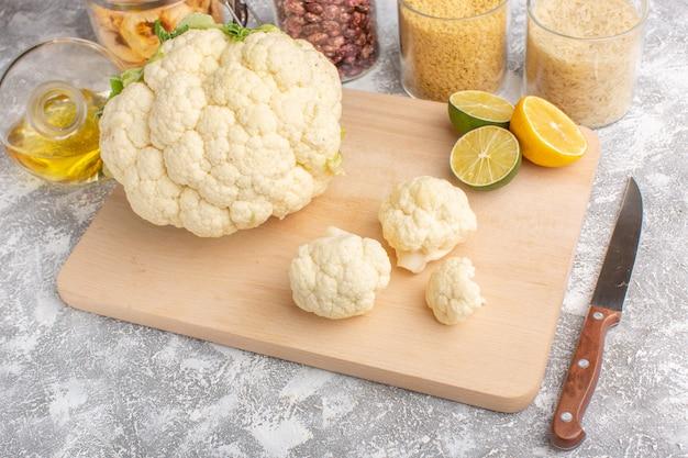 白色光の背景にレモンと油を添えた新鮮なカリフラワーの正面図野菜料理の生の色