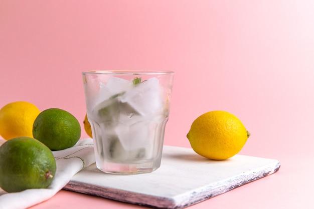 Вид спереди свежего холодного лимонада со льдом внутри стакана вместе со свежими лимонами на розовой стене