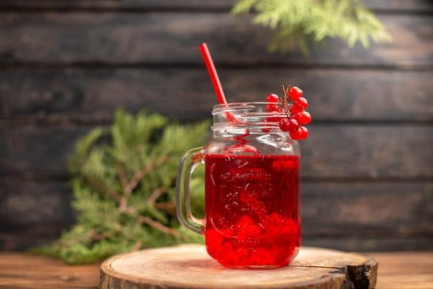 木製のまな板にチューブを添えたグラスに入った新鮮なカシス ジュースの正面図