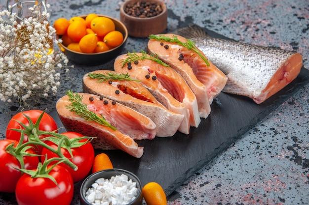 ダークカラーのトレイに緑の新鮮なカット生魚の正面図青黒のミックスカラーテーブルにスパイスキンカンオイルボトル