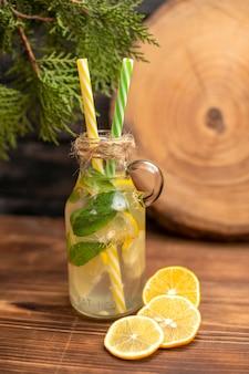 Вид спереди свежей воды для детоксикации в стакане с трубками и лимонным лаймом на деревянном столе