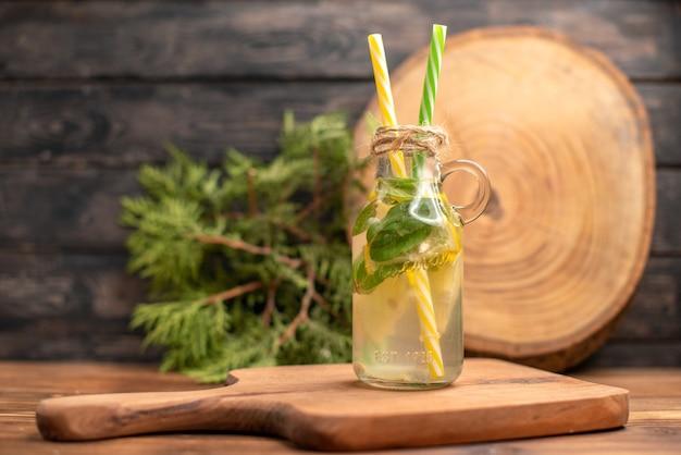 ガラスの新鮮なデトックス水の正面図は、茶色のテーブルの上の木製のまな板にチューブを添えて提供しています
