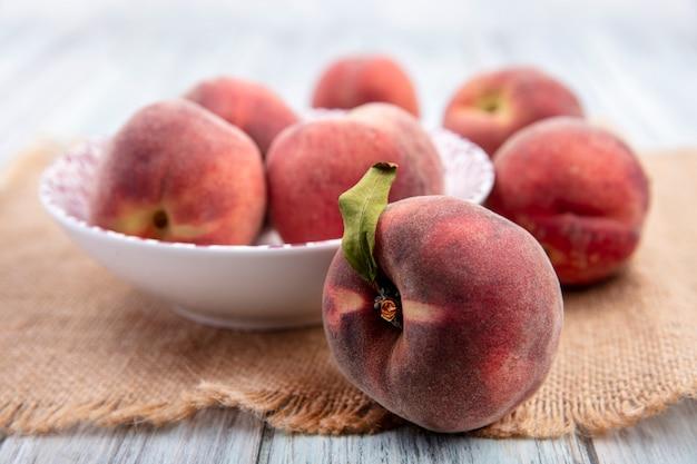 白い表面に分離された桃と白いボウルに新鮮なジューシーでおいしい桃の正面図