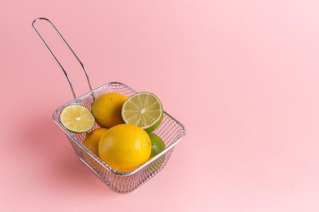 Вид спереди свежих лимонов цитрусовых внутри фритюрницы на розовой стене