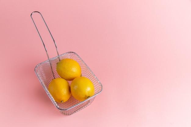 ピンクの壁のフライヤーの中の新鮮なレモン柑橘類の正面図