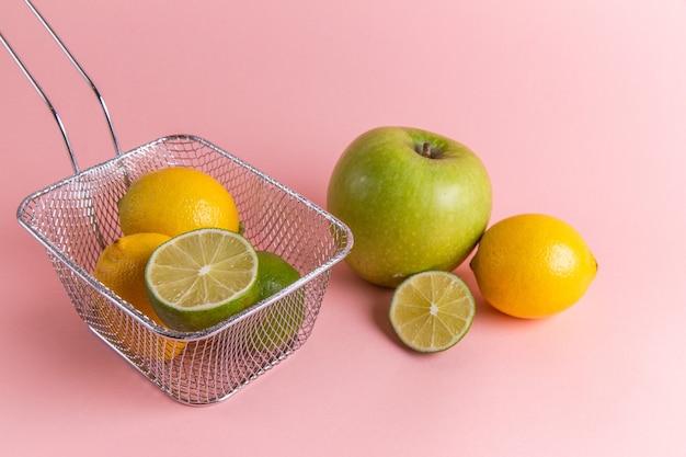 ピンクの壁にリンゴとフライヤー内の新鮮なレモン柑橘類の正面図