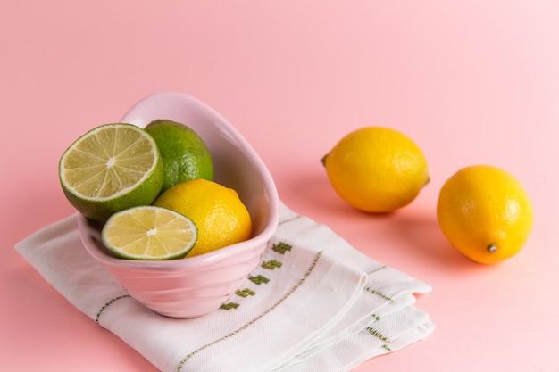 淡いピンクの壁のプレートの内側にスライスしたライムと新鮮なレモンの正面図