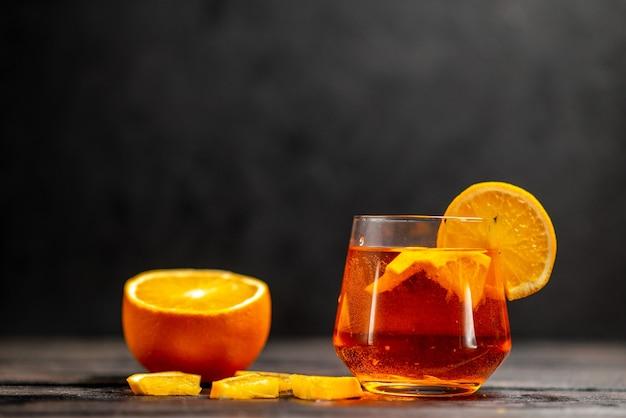 暗いテーブルの上のオレンジ色のライムとガラスの新鮮な自然のおいしいジュースの正面図