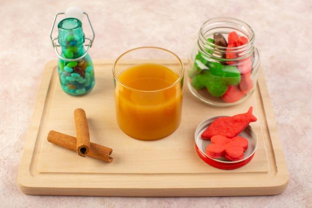 Вид спереди свежего персикового сока, сладкого и вкусного с красочным печеньем внутри, может с конфетами и палочками корицы