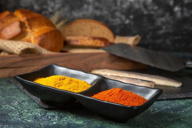 Вид спереди свежей сырой нарезанной рыбы на черной деревянной разделочной доске, специи и черный хлеб на поверхности смешанных цветов