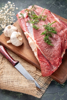 暗い色の背景にヌードカラータオルの茶色の木製まな板ナイフの新鮮な生の赤身の肉緑のニンニクレモン塩の正面図
