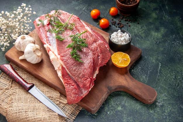 新鮮な生の赤身の肉緑のニンニクレモン塩茶色の木製まな板ナイフヌードカラータオルトマトコショウ暗い色の背景の正面図