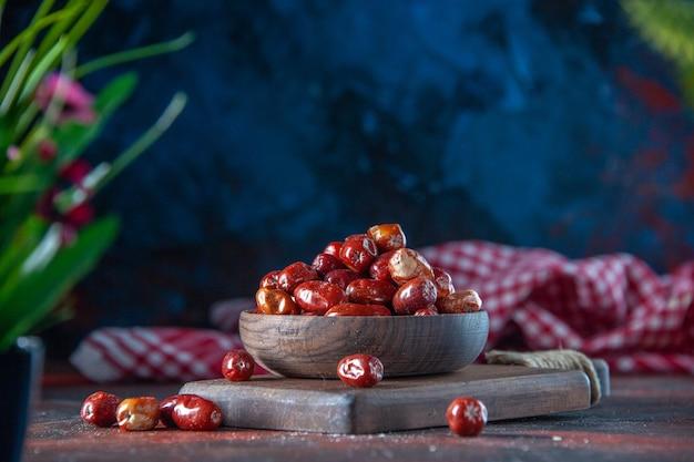 혼합 색상 배경의 나무 커팅 보드에 있는 그릇에 신선한 생 은베리 과일의 전면 보기