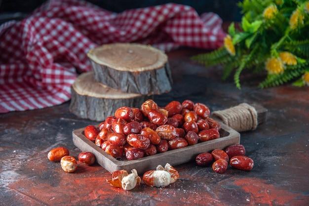혼합 색상 배경에 나무 쟁반 꽃 냄비 빨간색 벗겨진 수건의 내부 및 외부 신선한 생 은베리 과일의 전면 보기