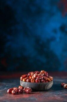 여유 공간이 있는 혼합 색상 배경에 있는 그릇 내부와 외부의 신선한 생 은베리 과일의 전면 보기