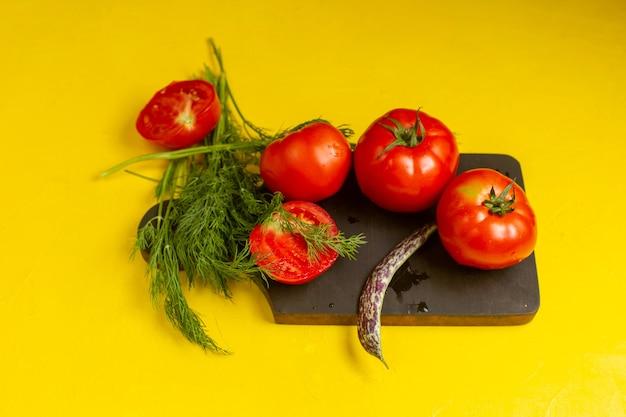Вид спереди свежих красных помидоров, свежих и спелых овощей с зеленью и фасолью на желтой стене