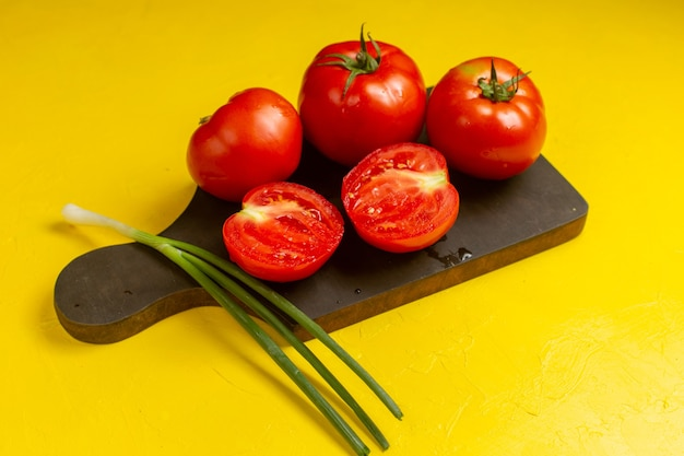 黄色い壁にネギと新鮮な新鮮な赤いトマトの正面図