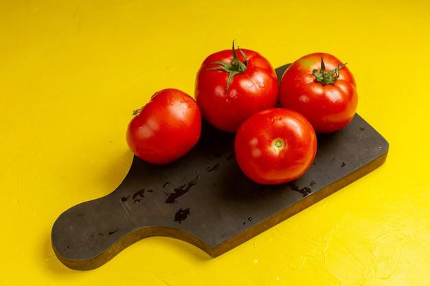 Вид спереди свежих красных помидоров на желтой поверхности