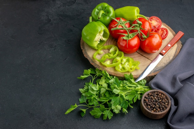 新鮮なトマトとピーマンを黒い表面に緑の束を木の板に乗せた正面図