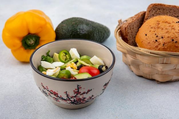 白い表面にパンのアボカドと黄色のピーマンのバスケットとボウルにペッパーキュウリトマトを含む新鮮な野菜サラダの正面図