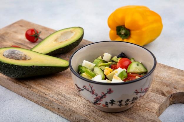 白い表面にアボカドスライスと黄色のピーマンと木製のキッチンボード上のボウルにキュウリトマトと新鮮野菜のサラダの正面図