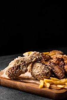 Вид спереди жареных куриных ножек с картофелем фри и копией пространства
