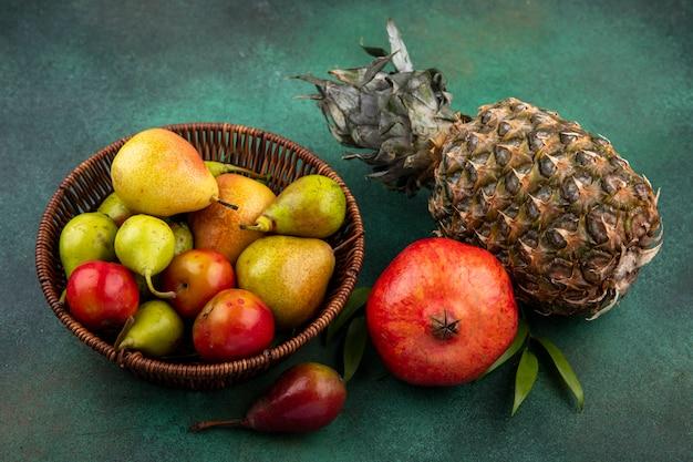 Вид спереди фруктов, как персик, яблочная слива в корзине с гранатом и ананасом на зеленой поверхности