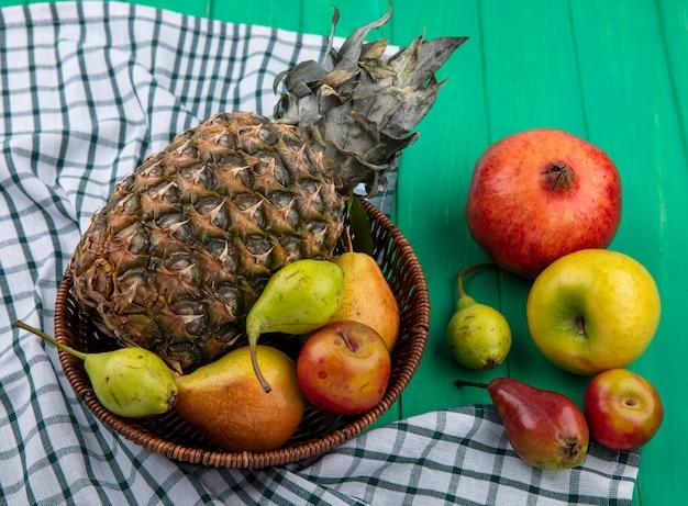 Вид спереди фруктов в виде ананасово-персиковой сливы в корзине на клетчатой ткани с гранатовым яблоком на зеленой поверхности