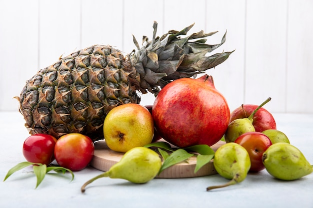 Вид спереди фруктов в виде сливы персика и граната на разделочной доске и с яблоком и ананасом на белой поверхности