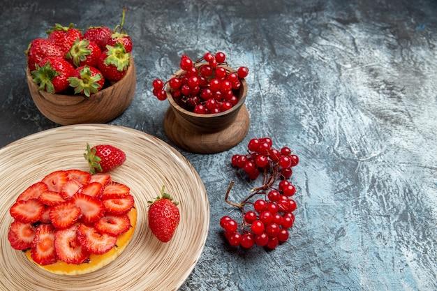 暗い表面に新鮮なイチゴとフルーティーケーキの正面図