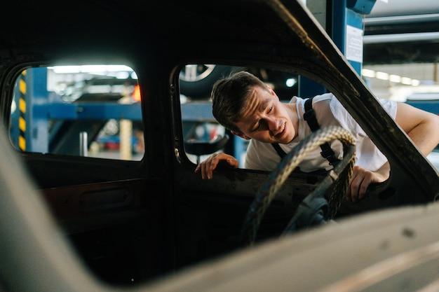 자동차 수리에서 오래된 차의 내부를 검사하는 제복을 입은 좌절한 젊은 서비스 남자의 전면 보기 ...