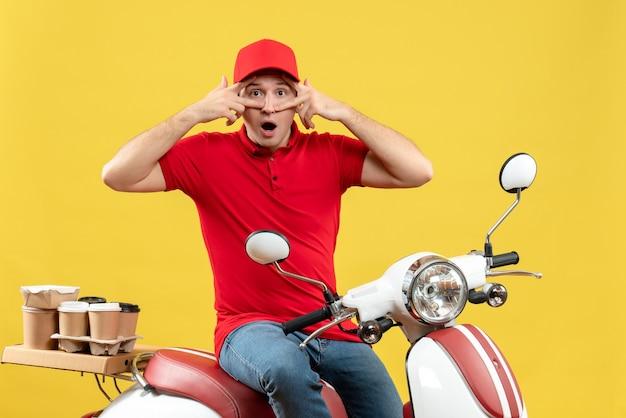 黄色の背景に注文を配信する赤いブラウスと帽子を身に着けている面白いと感情的な若い男の正面図